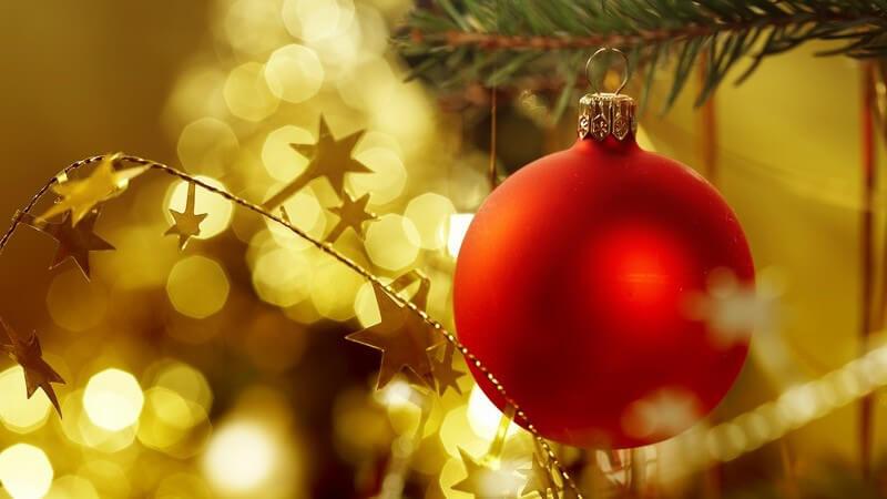 Rote Christbaumkugel an Weihnachtsbaum, im Hintergrund goldener Baumschmuck