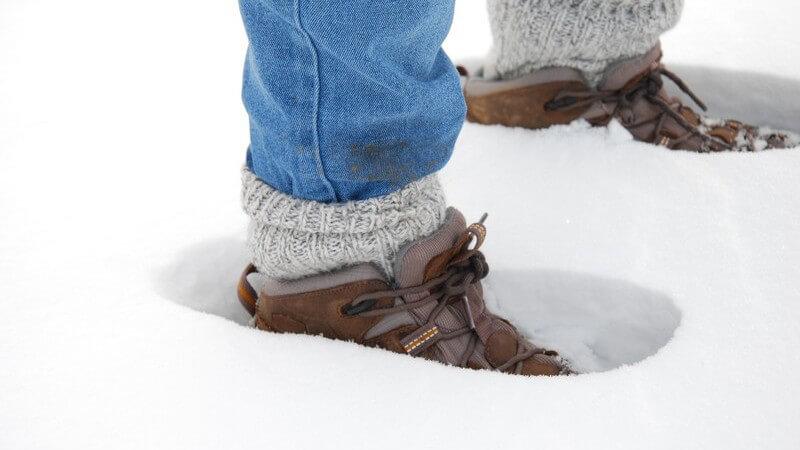 Beine in Jeans, Winterschuhe im Schnee