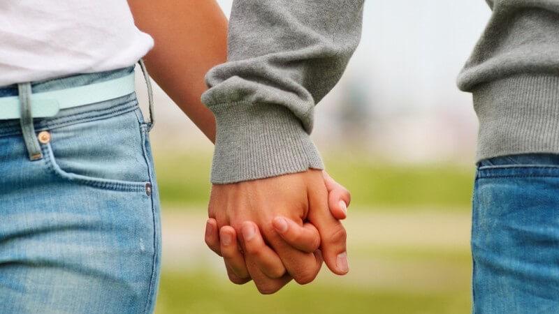 Nahaufnahme Paar Hand in Hand beim Spazierengehen