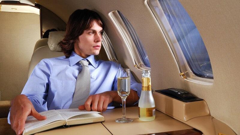 Junger Mann in blauem Hemd mit Krawatte blickt in 1. Klasse im Flugzeug zum Fenster raus, liest Buch und trinkt Sekt