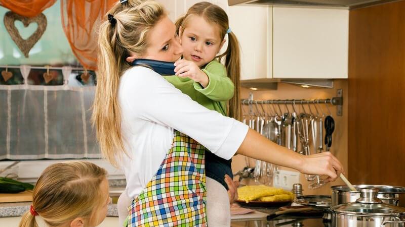 Junge Mutter an Herd und mit zwei Töchtern, gestresst