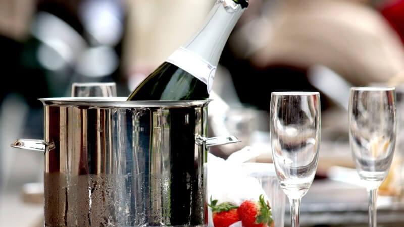 Offener Champagner in silbernem Sektkübel auf silbernem Tisch mit zwei Gläsern und Erdbeeren