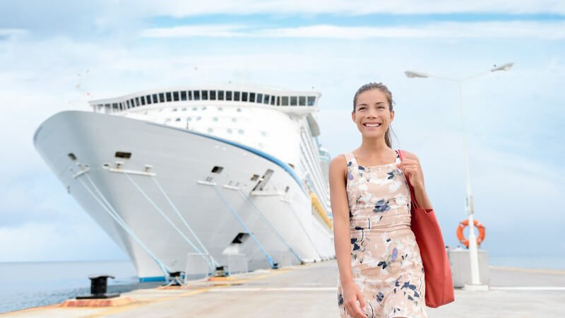 Großes weißes Kreuzfahrtschiff liegt im Hafen, junge Frau in Sommerkleid geht shoppen