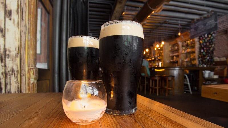 Zwei Pint-Gläser mit dunklem Bier (Stout) neben Kerze in Irish Pub