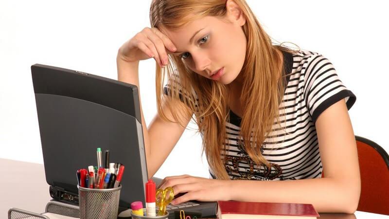 Schülerin erschöpft vor ihrem Notebook, neben ihr Bücher, weißer Hintergrund