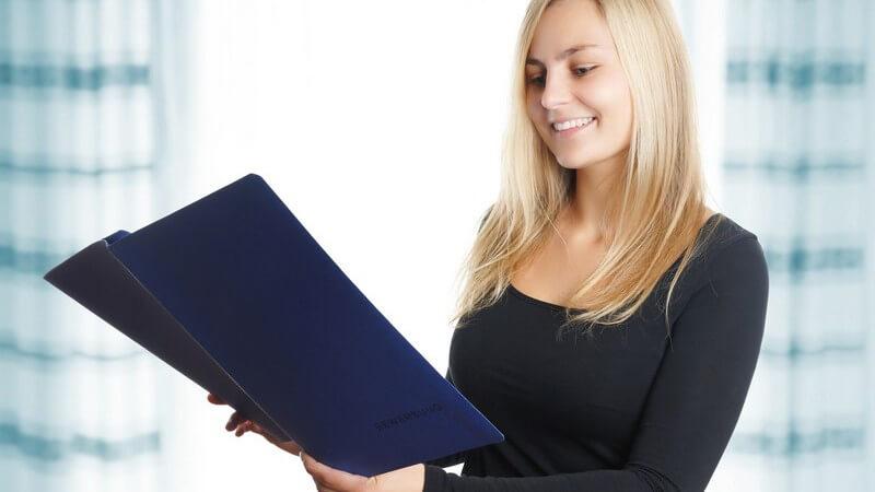 Junge Frau mit langen blonden Haaren beim Lesen in einer blauen Bewerbungsmappe