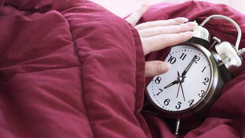 Wecker zeigt sieben Uhr, Hand schaut aus Bettdecke hervor und macht ihn aus