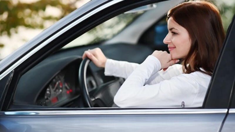 Verkehr - Junge Frau sitzt gelassen am Steuer ihres Autos