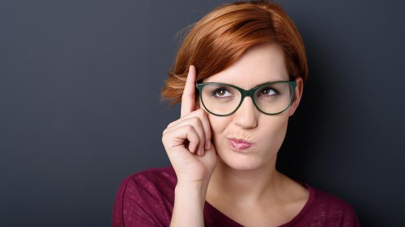 Frau mit rotbraunen Haaren hält nachdenkend den Zeigefinger neben ihre Brille und verzieht den Mund, grauer Hintergrund