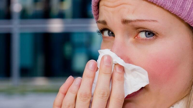 Junge blonde Frau mit rosaner Mütze putzt sich mit Taschentuch die Nase