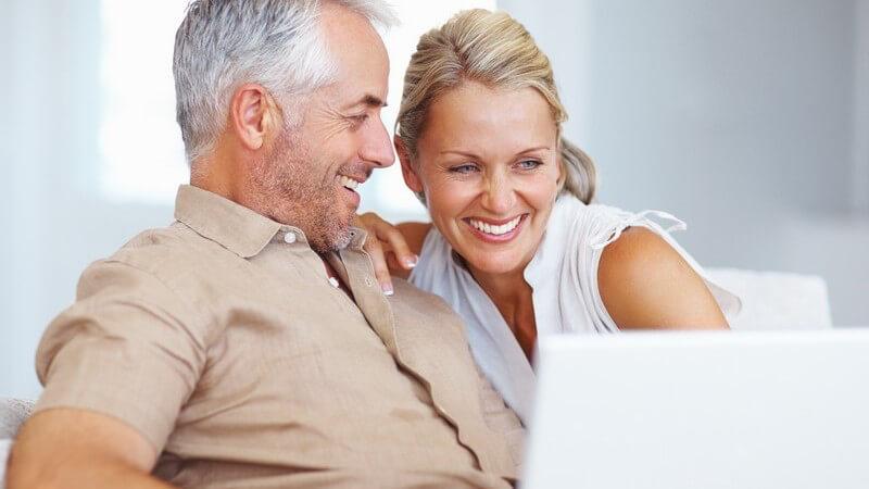 Älteres lachendes Paar auf Couch hinter Notebook
