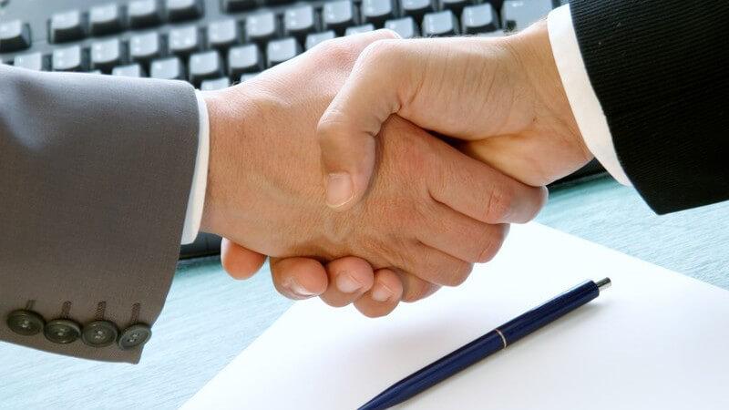 Hände in Anzug greifen ineinander, dahinter Tastatur, Papier und Stift