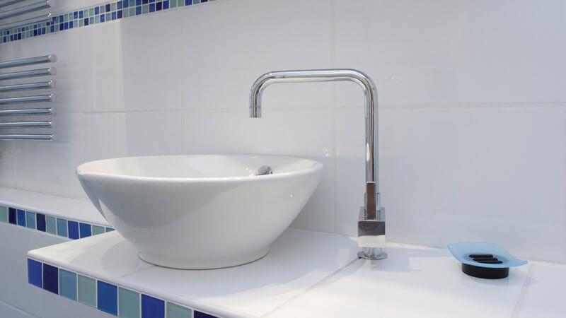 Modernes Waschbecken mit Armatur und Mosaikfliesen