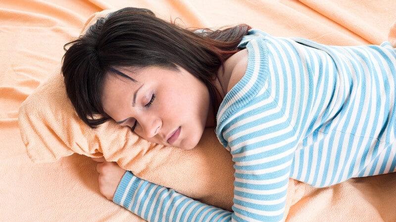 Dunkelhaarige Frau liegt auf dem Bauch im Bett und schläft