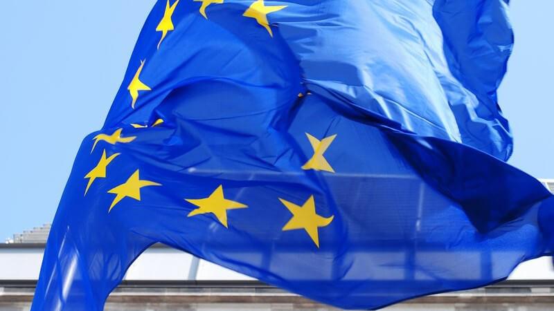 Wehende Europafahne oder EU-Flagge vor Himmel und Haus