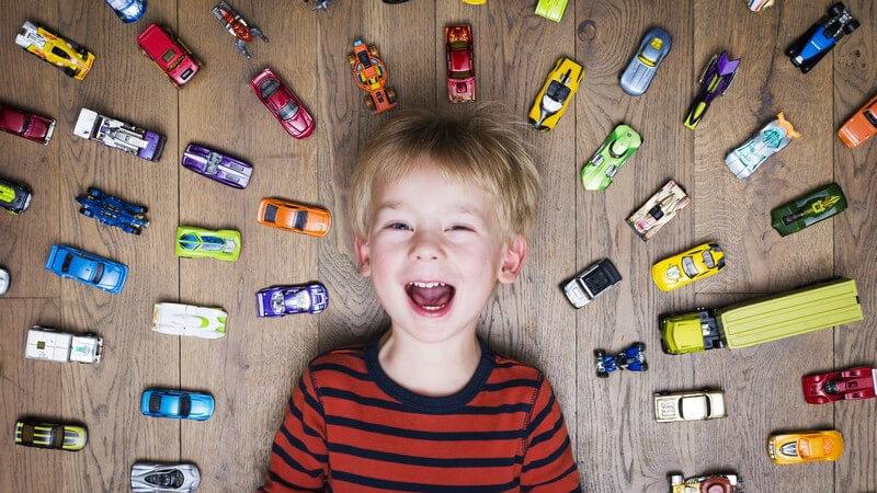 Junge liegt auf dem Boden, umringt von zahlreichen Spielzeugautos