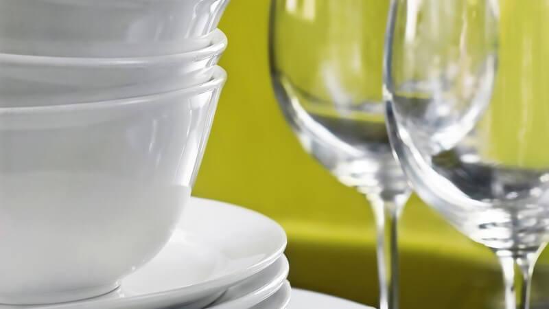 Weißes Porzellangeschirr, daneben zwei Weingläser