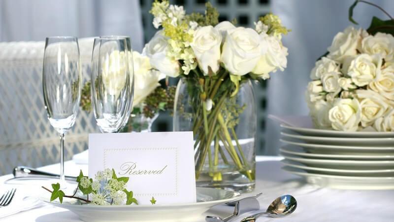 Gedeckter, reservierter Tisch mit weißen Rosen zur Hochzeit