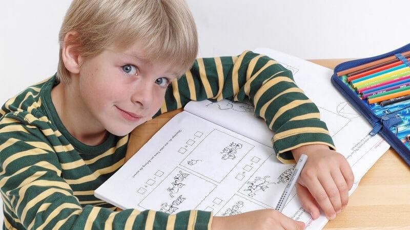 Junger Schüler am Schreibtisch macht Hausaufgaben