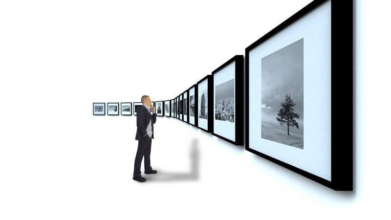 Mann im schwarzen Anzug begutachtet schwarz weiße Fotografien an weißer Wand
