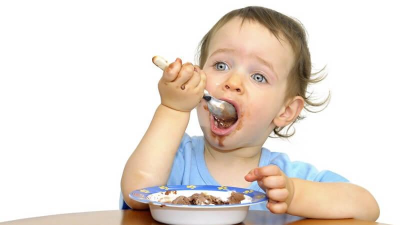 Kleinkind sitzt am Tisch und isst, Gesicht vollgeschmiert