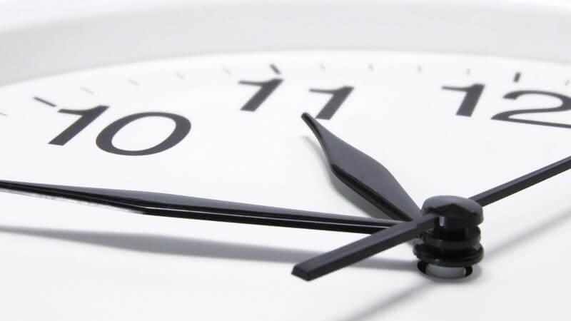 Nahaufnahme Ausschnitt Wanduhr, zeigt Uhrzeit viertel vor elf