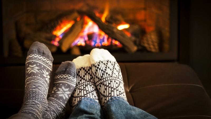 Mit Wollsocken vor dem warmen Kaminfeuer liegen