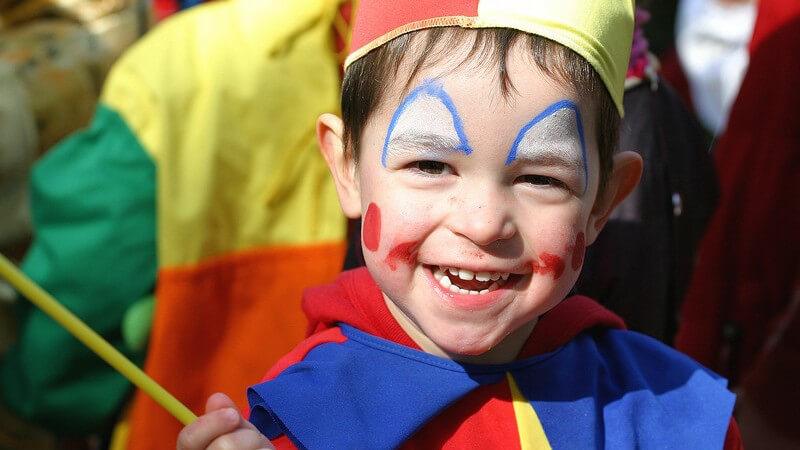 Kleiner lächelnder Junge als Clown verkleidet und geschminkt