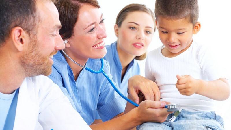 Gesundheitsvorsorge, ein Arzt und zwei Krankenschwestern behandeln kleinen Jungen, mit Stetoskop, lächelnd, heller Raum