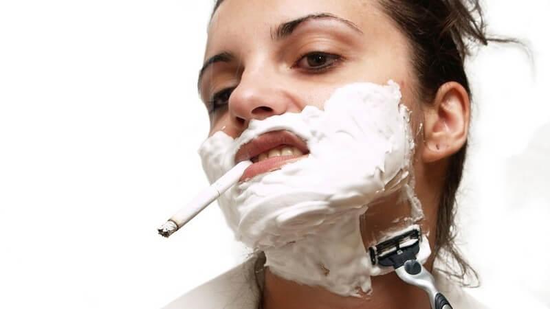 Junge Frau mit Rasierschaum im Gesicht und Zigarette im Mund rasiert sich mit Nassrasierer