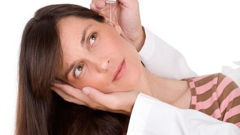 Frau hält Kopf schief, linke Hand mit Kittel stützt ihren Kopf, rechte Hand flößt ihr Ohrentropfen mit Pipette ein