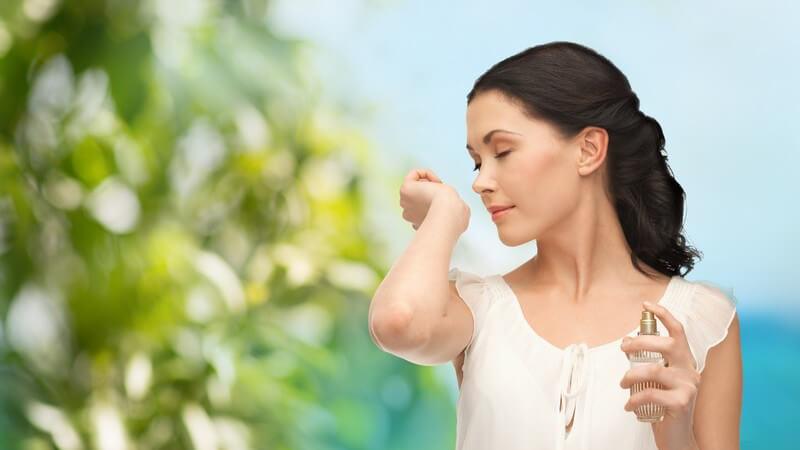 Sommerduft - junge Frau mit Parfum-Flakon riecht an ihrem Handgelenk