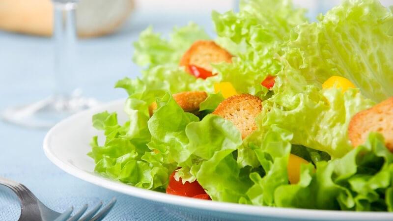 Grüner Salat mit Crutons, daneben eine Gabel, dahinter Brot und ein Glasstiel