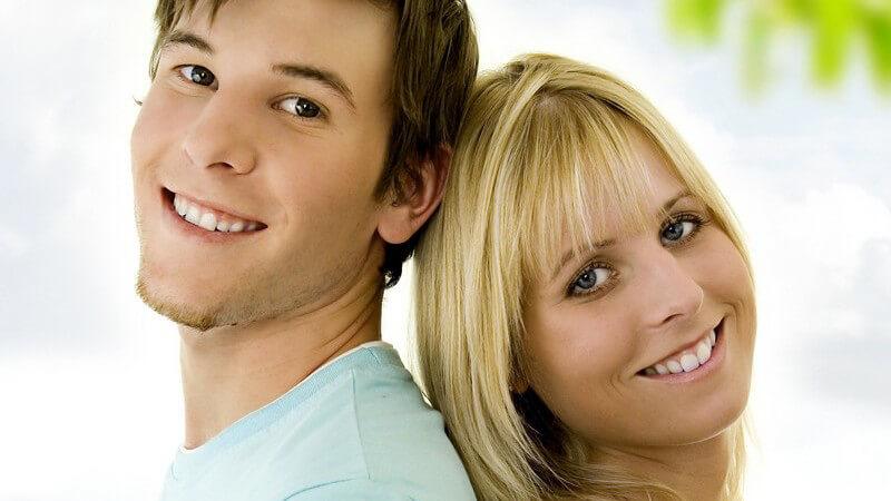 Junges Paar, Rücken an Rücken, lächeln in Kamera