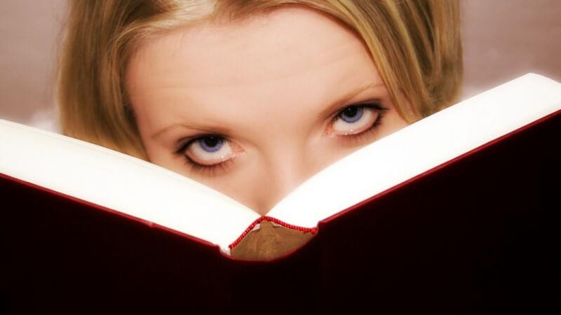 Augen einer jungen Frau, sie schaut aus ihrem Buch hervor