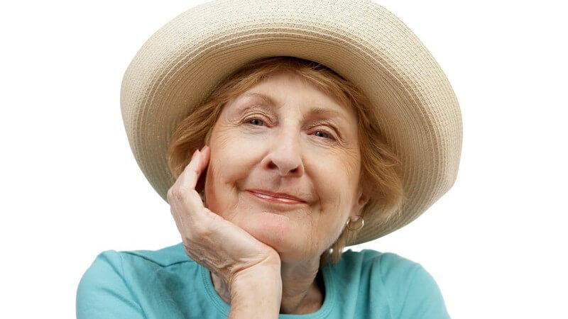 Reife Frau mit Hut lächelt in die Kamera, stützt Kinn auf ihre Hand