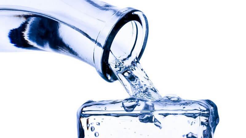 Eine Glasflasche füllt ein Glas Wasser bis zum Anschlag
