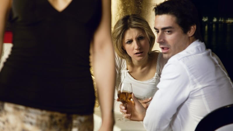 Paar am Tisch, er guckt vorbeigehender Frau lustvoll hinterher, seine Partnerin ist sauer