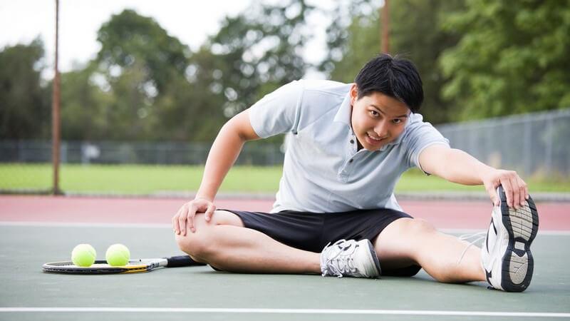 Junger Mann im Sportoutfit sitzt auf Tennisplatz und dehnt sich vor dem Tennisspiel