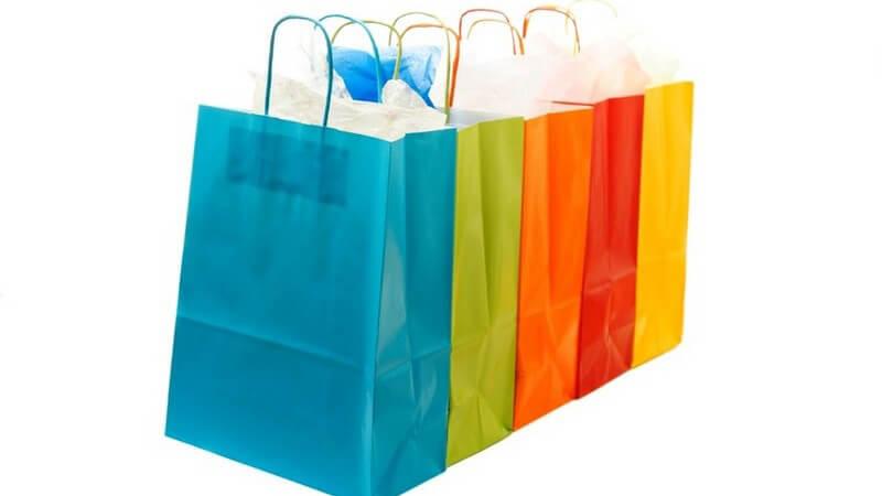 Fünf Einkaufstaschen, Papiertaschen, vom Shopping, türkis, grün, orange, rot, gelb, vor weißem Hintergrund