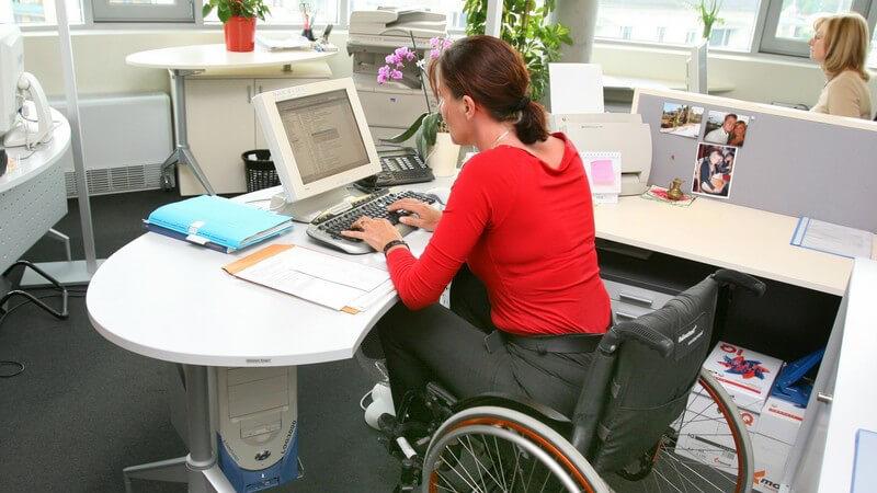 Frau im Rollstuhl am Computer im Büro