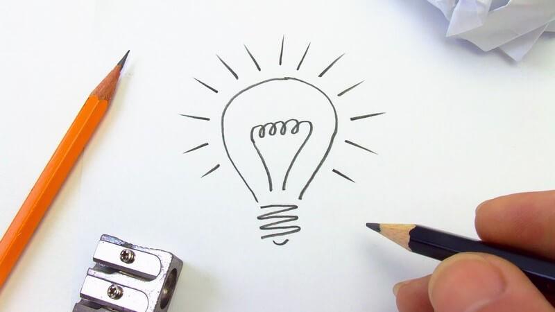 Glühbirne mit Bleistift auf Papier gezeichnet, daneben Bleistift, Spitzer, zerknülltes Papier