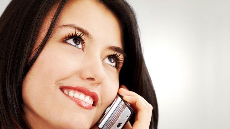 Dunkelhaarige, lächelnde Frau telefoniert mit Handy