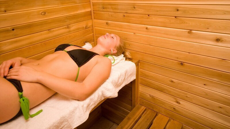 Blonde Frau im schwarz-grünen Bikini liegt auf einer Saunabank auf einem weißen Handtuch