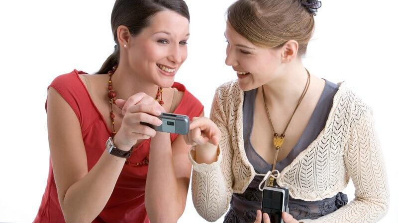 Junge Frau zeigt anderer Frau ihr Handy, Handyfoto, Unterhaltung, vor weißem Hintergrund