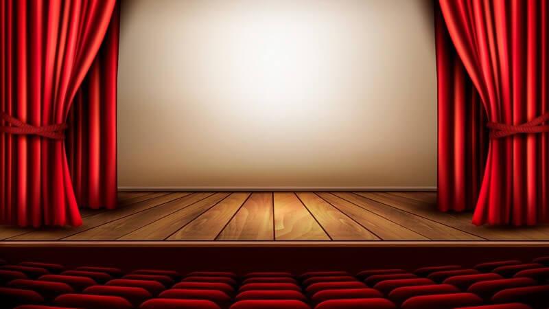 Leerer Theatersaal mit Bühne, rotem Vorhang und Sesseln