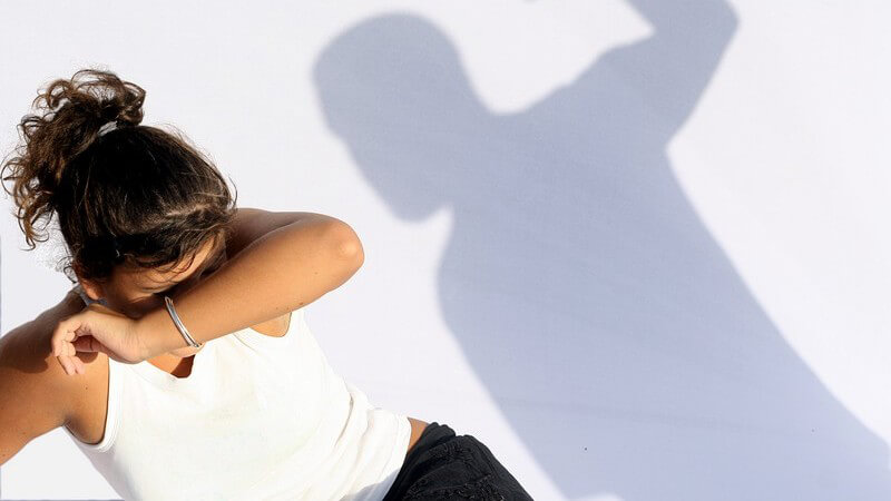 Brünettes Mädchen hält Arm schützend vors Gesicht, dahinter Schatten eines Mannes mit erhobener Faust