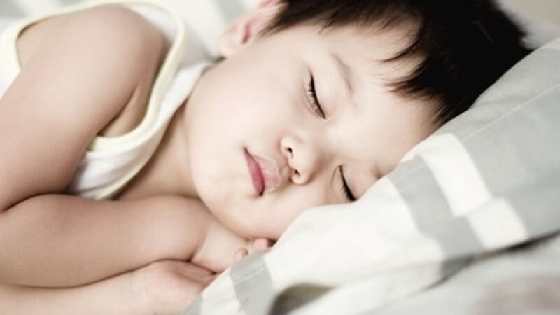 Kleiner Junge schläft friedlich auf der Seite