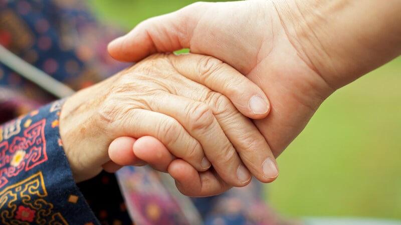Junge Hand hält die faltige Hand einer alten Frau in bunt-verzierter Kleidung