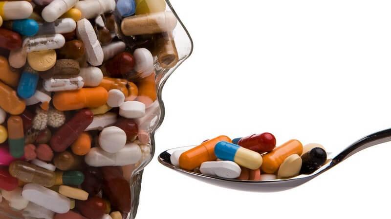 Glasmodell menschlicher Kopf gefüllt mit bunten Pillen, Löffel mit Pillen wird an Mund gehalten